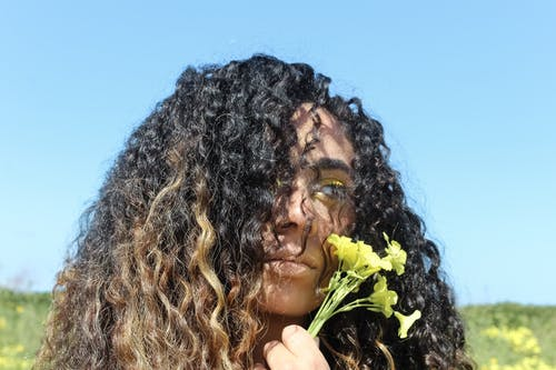 Close-Up Photo of Woman Holding Yellow Flower