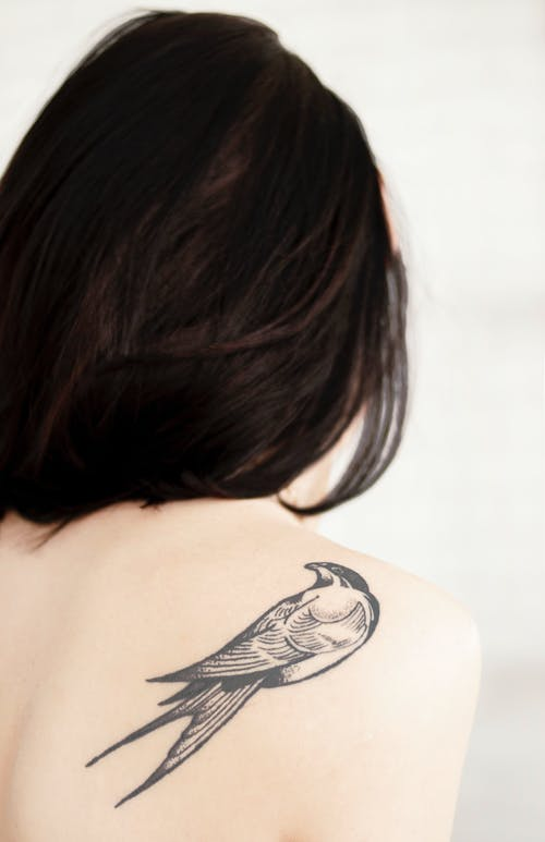 View of Woman's Back With Bird Tattoo on Right Shoulder