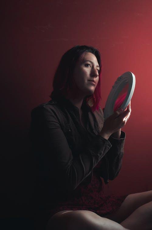 Kostenloses Stock Foto zu festhalten, frau, rotem hintergrund, schöne frau