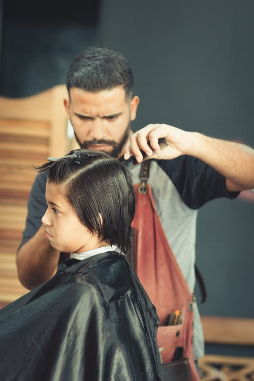 Man Cutting Hair of a Boy