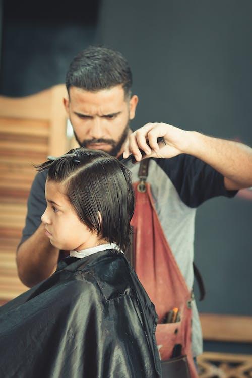 Man Cutting Hair of a Boy