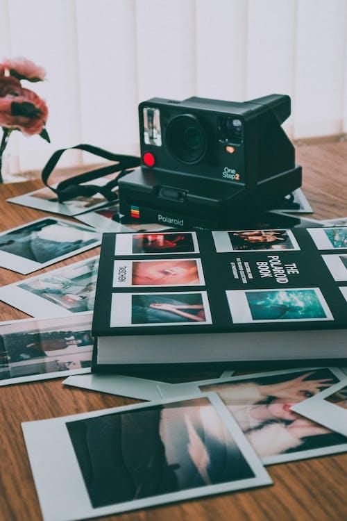 Photo of Polaroid Camera Near Book