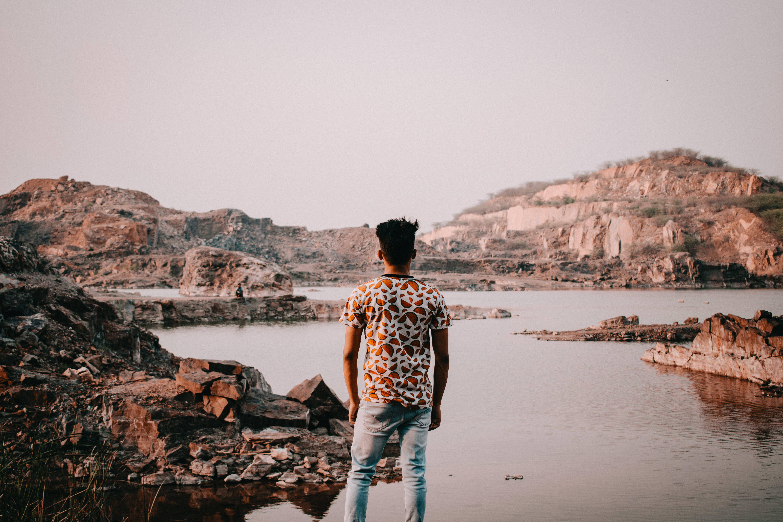 Photo of Man Standing Near Rocky Lake