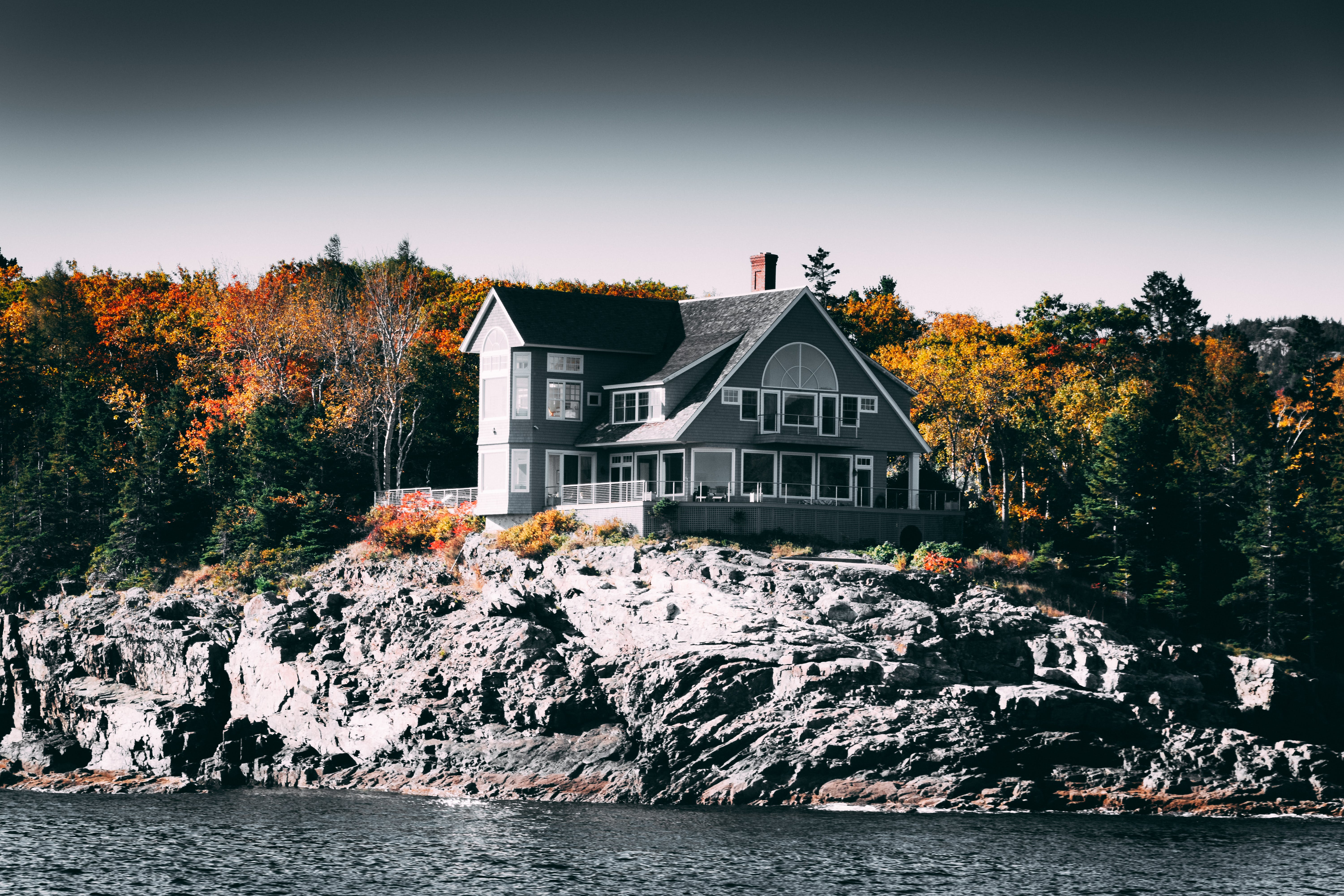 Gray and White House Beside Body of Water