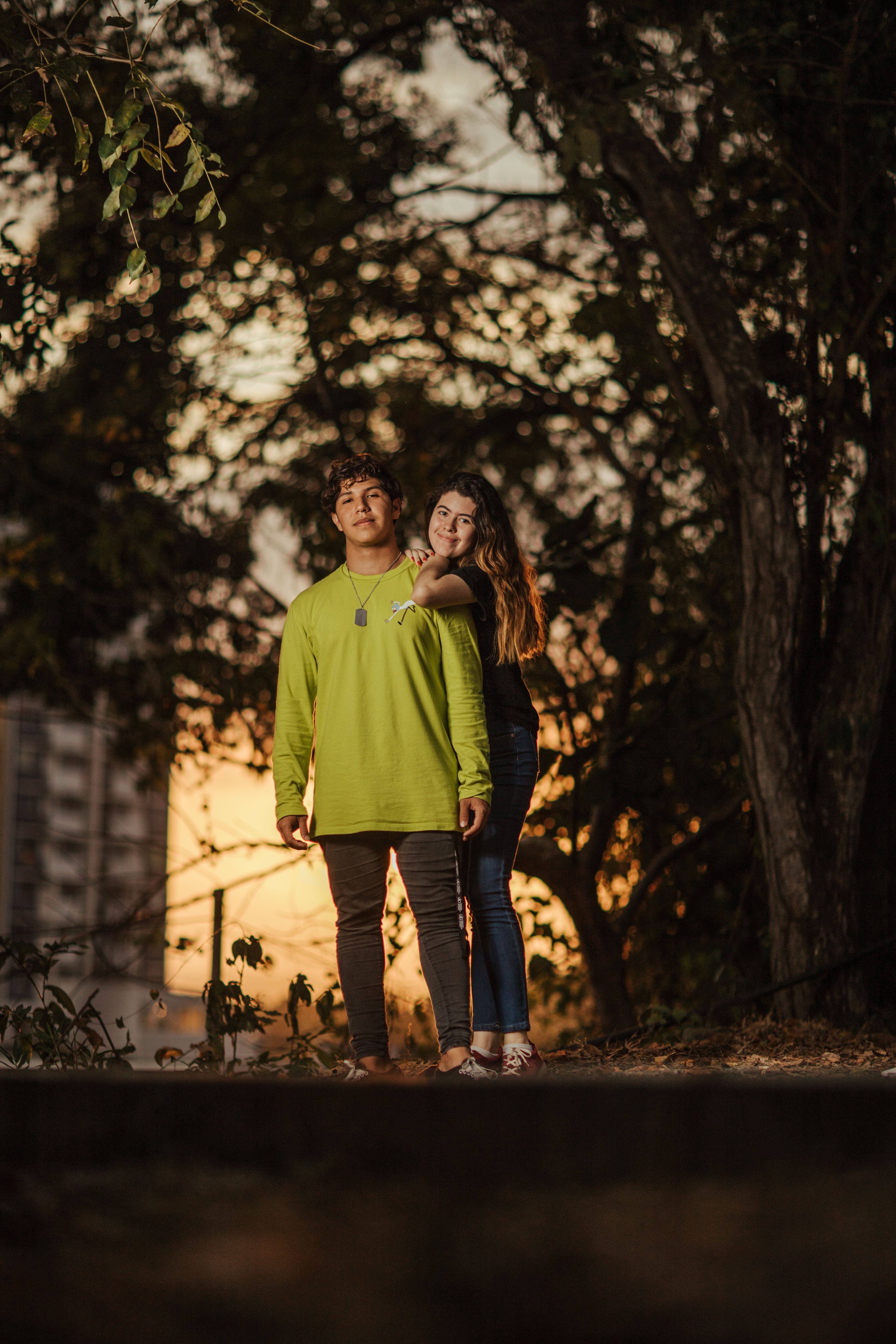 Photo of Smiling Couple Standing Under a Tree