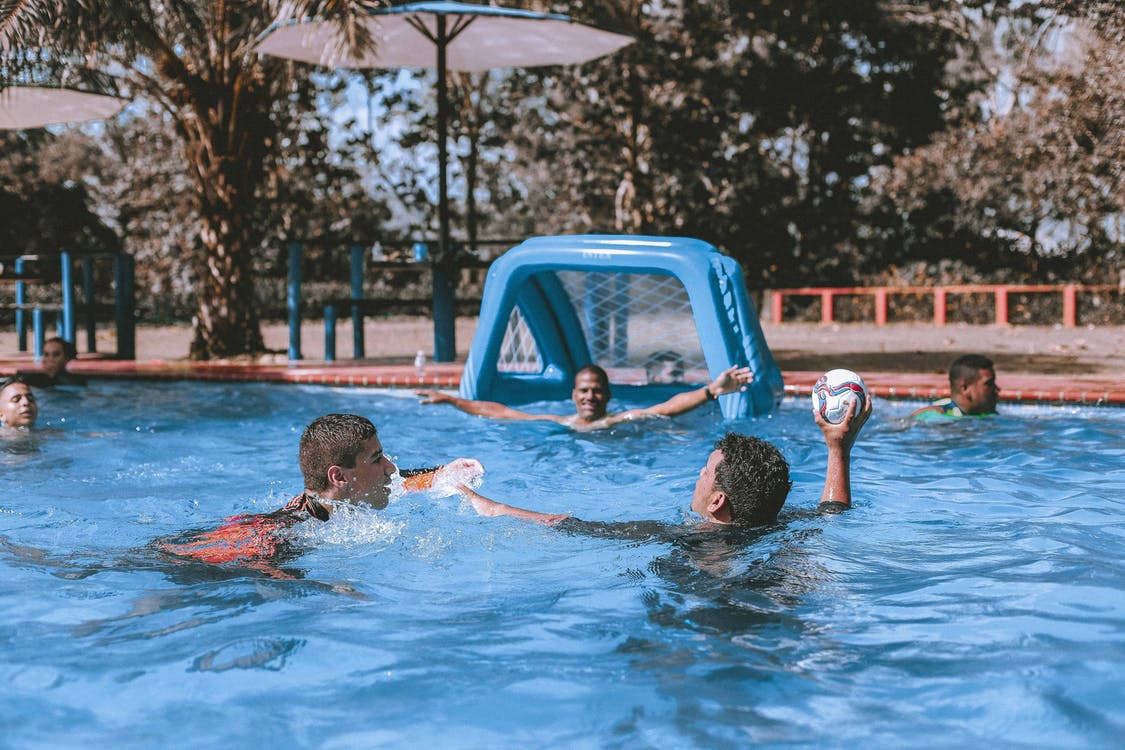 People on Swimming Pool Playing Ball