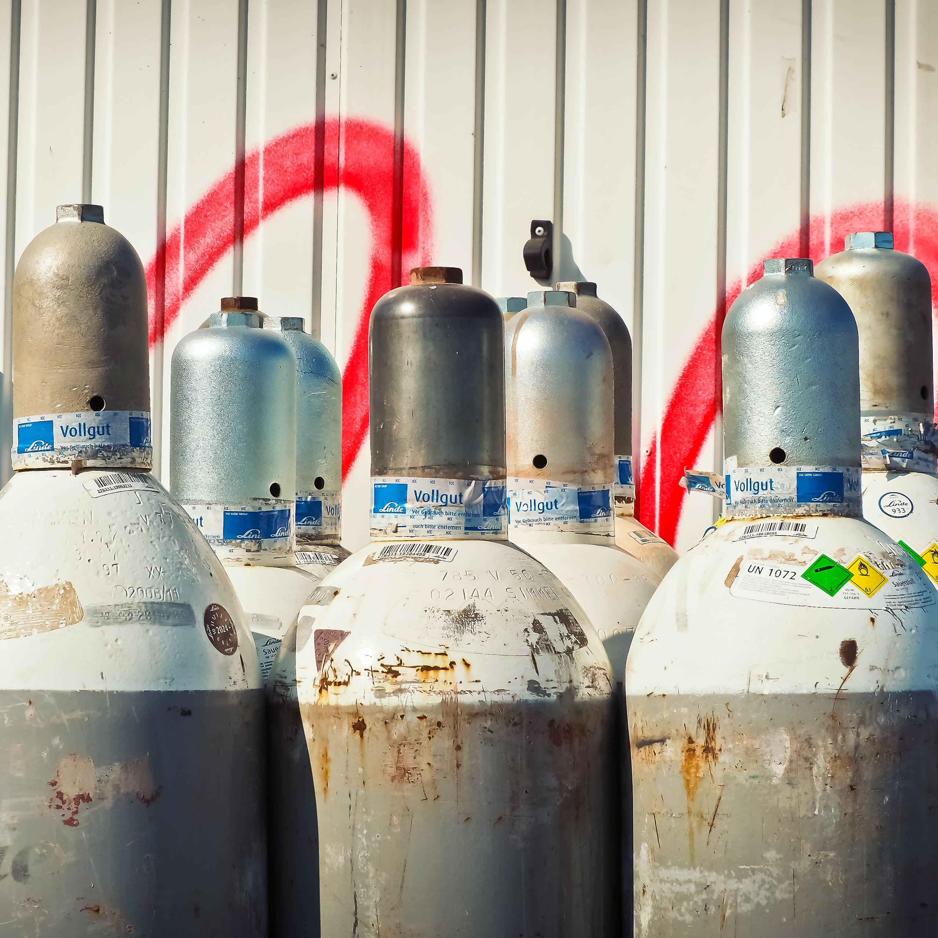 Gray Steel Gas Tanks Near White Steel Wall during Daytime