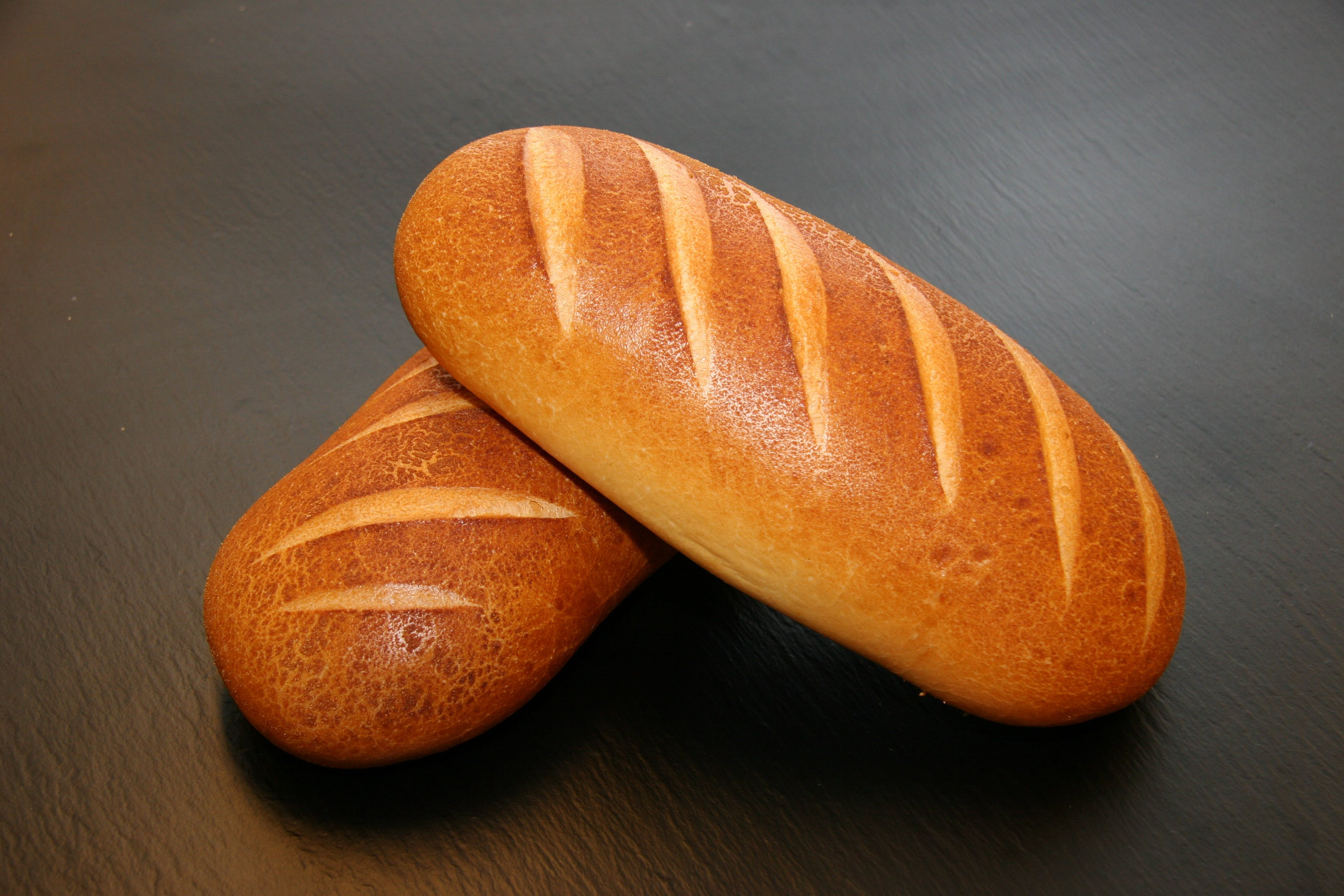 Two Brown Baked Breads on Table