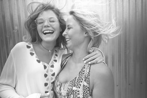 Grayscale Photo of Women Laughing With Their Eyes Closed
