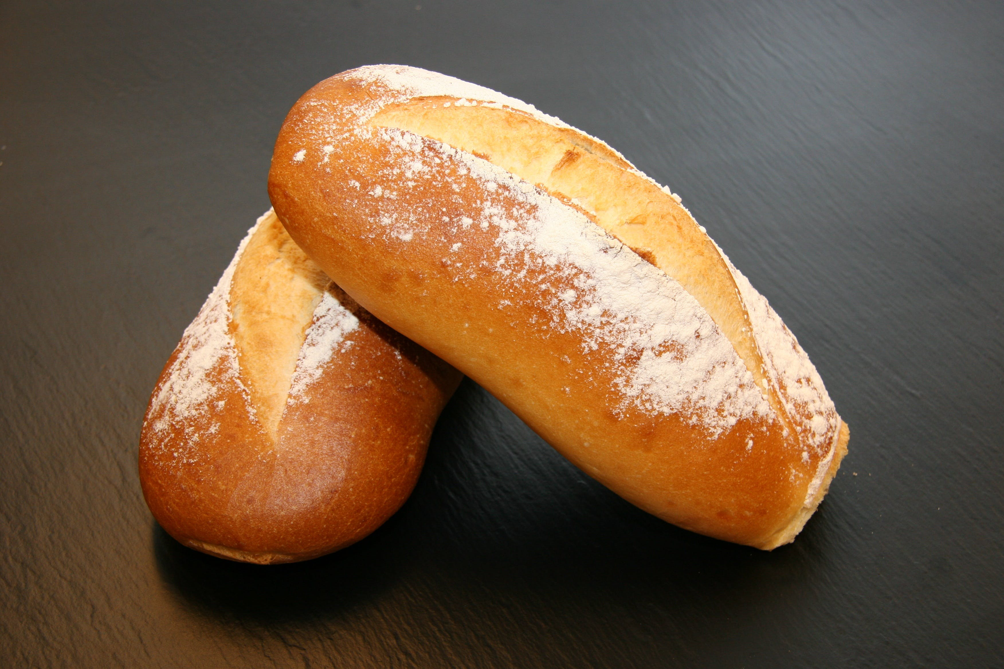 Two Baked Breads on Black Surface
