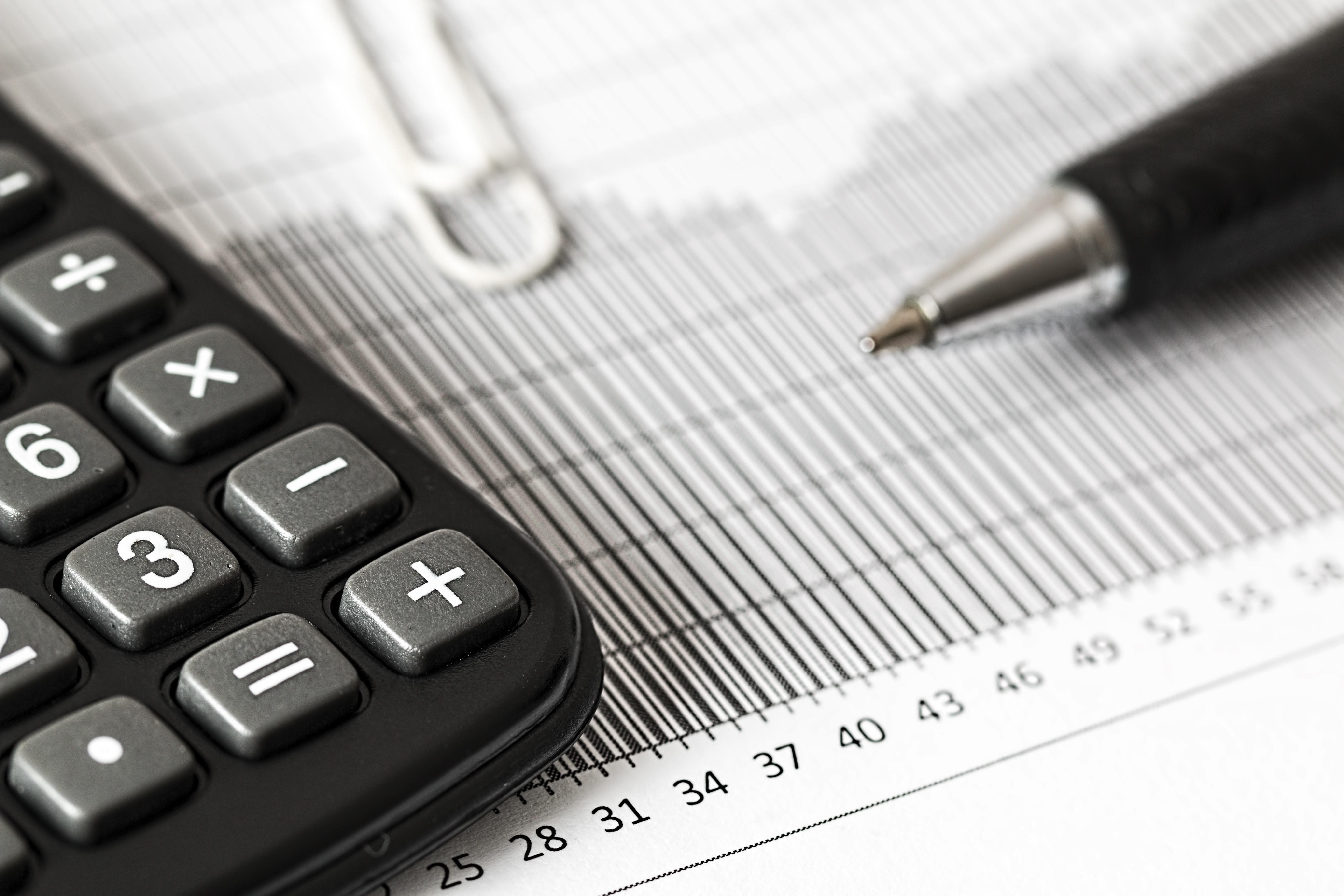 Imagem de caneta, papéis com números e calculadora para representar a prática de estudo de viabilidade