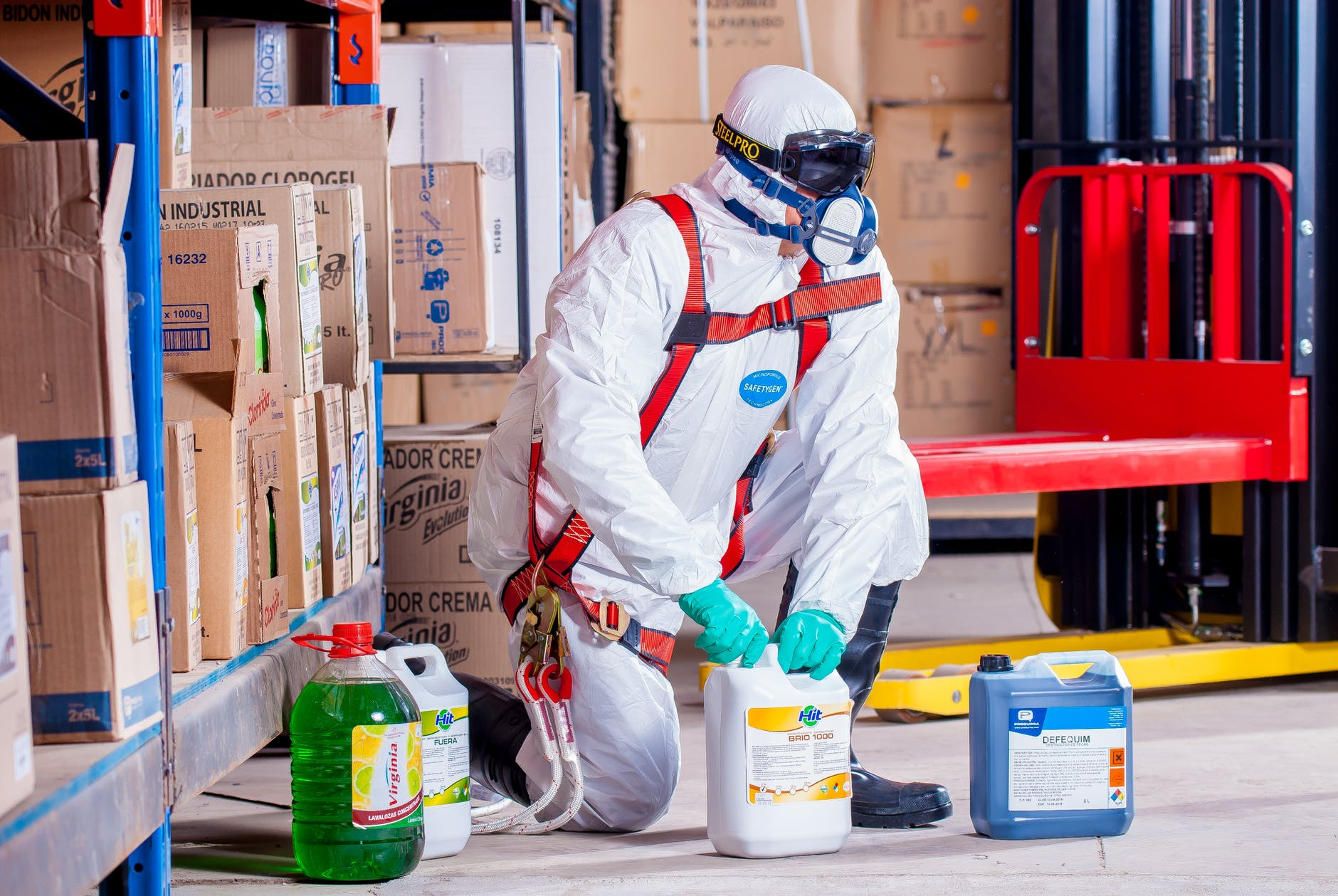 person wearing white suit holding weed killers
