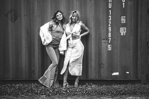 Grayscale Photography of Two Women Standing Near Intermodal Container