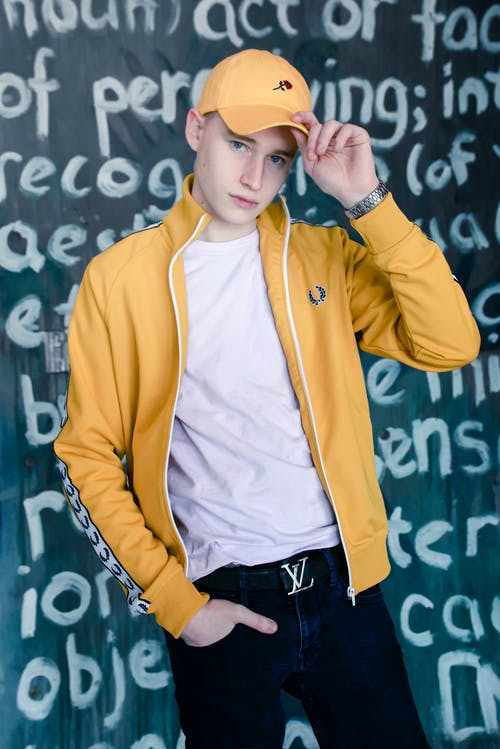 Man Standing Holding Yellow Cap