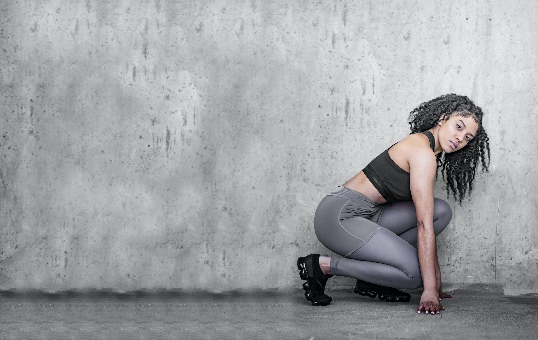 Woman In Grey Leggings Kneeling Near Wall