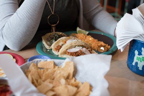 Person Sitting in Front of Tacos on Plate