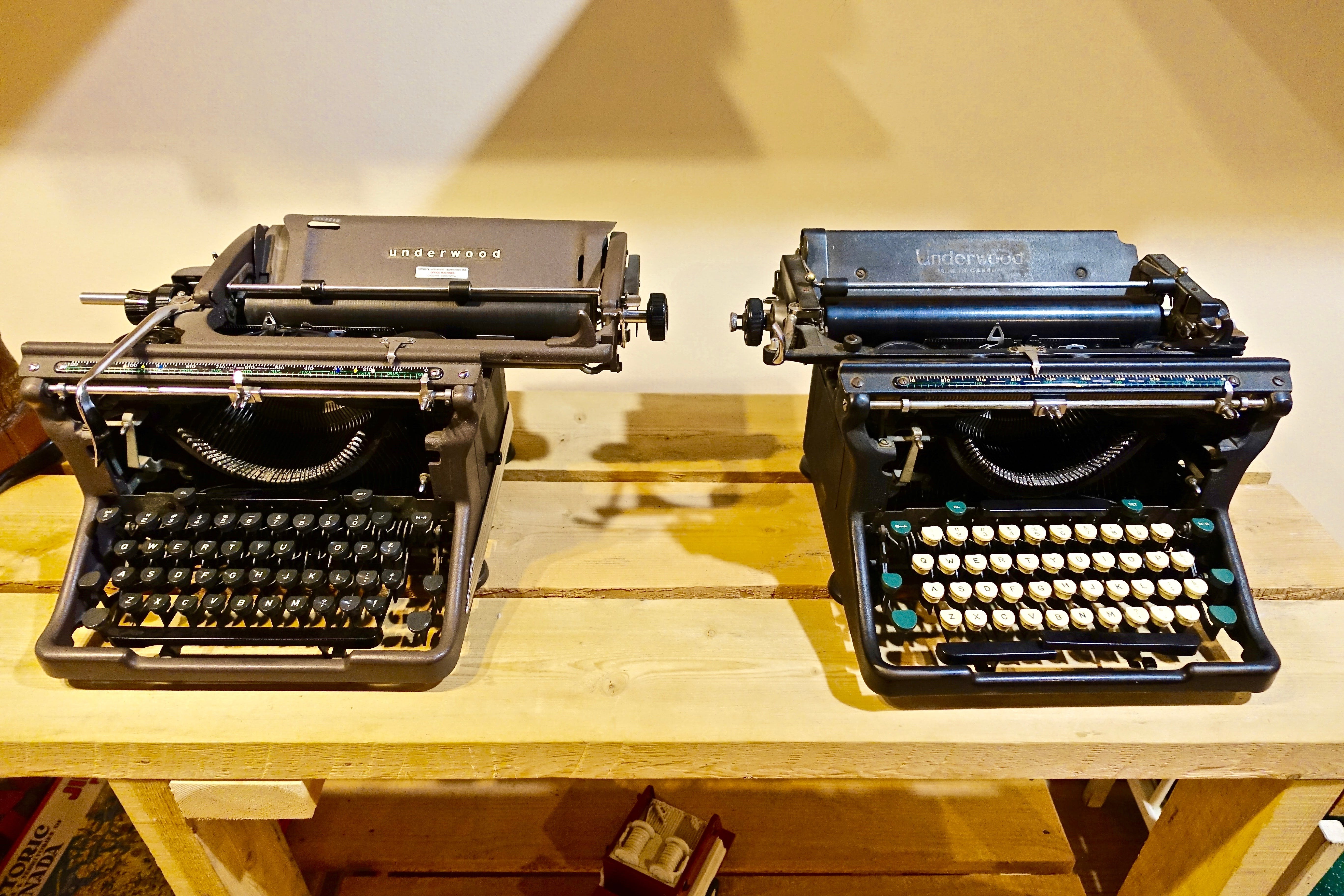 Two Black Typewriters on Wooden Table