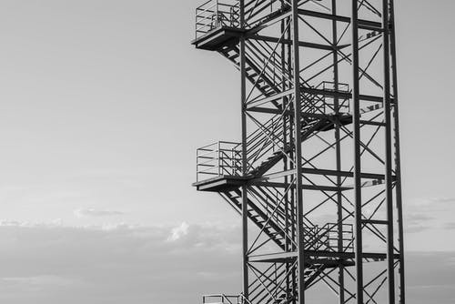 Industrial observation tower against cloudy sky