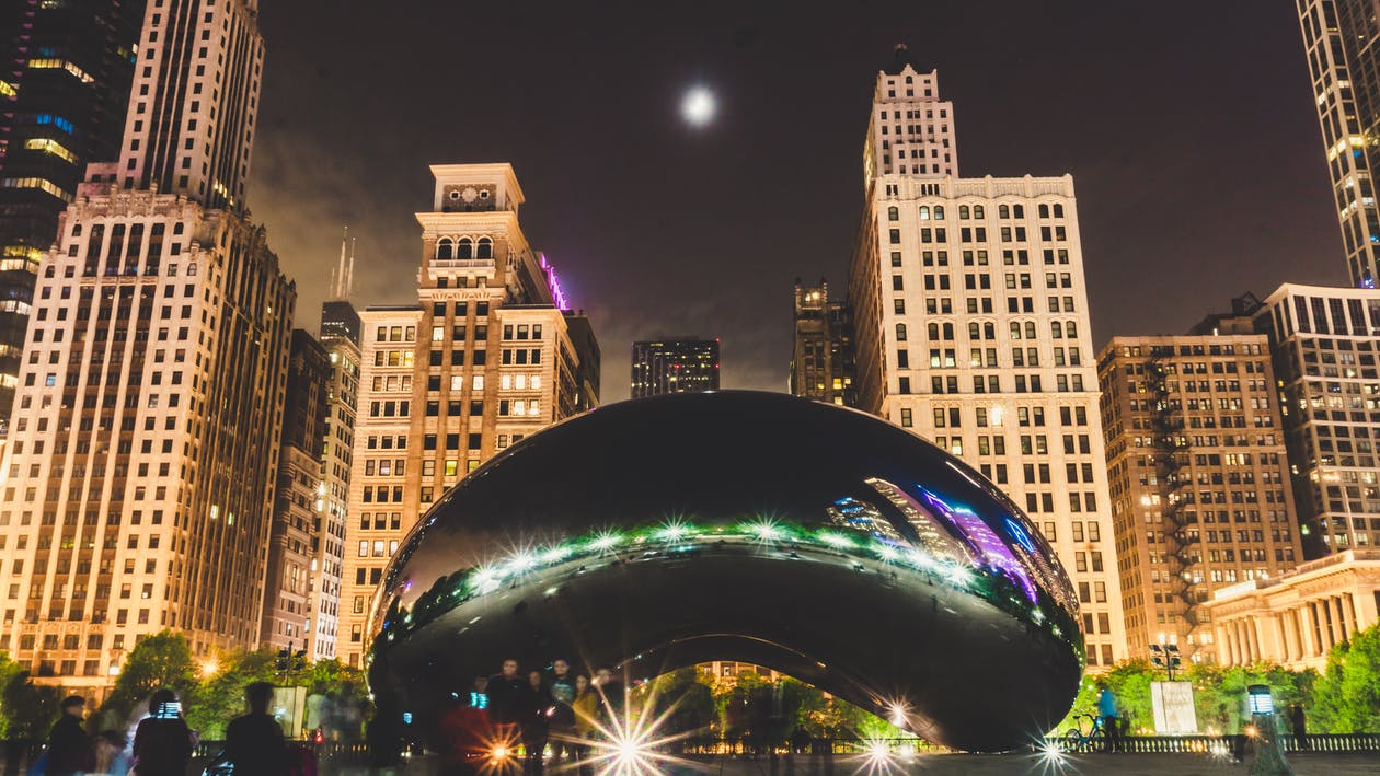 Cloud Gate in Front of High-rise Tower Buildings