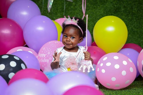 Toddler Girl Sitting On Ground Surrounded By Balloons