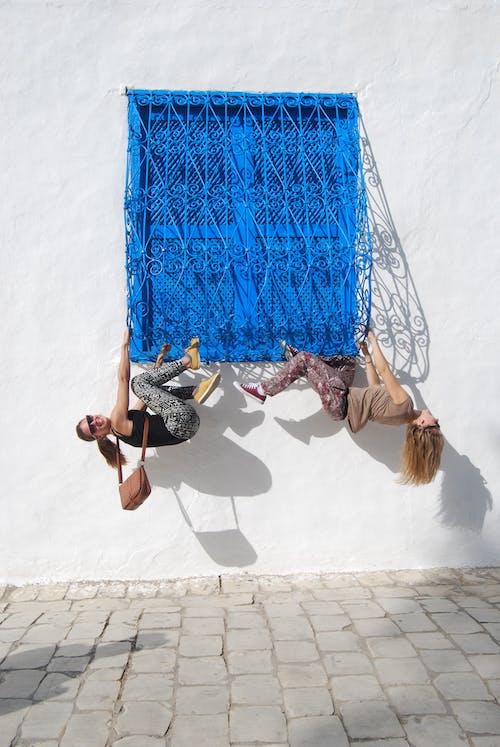 Two Women Clinging on Window Rails