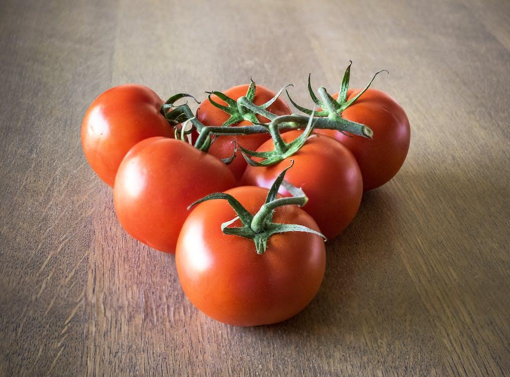 Sei Pomodori Arancioni Che Formano Triangolo Sulla Superficie Marrone