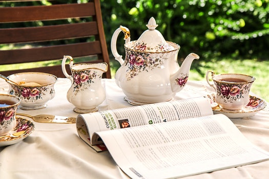 White and Pink Floral Ceramic Tea Set on White Textile Covered Table Beside White and Black Printed Book