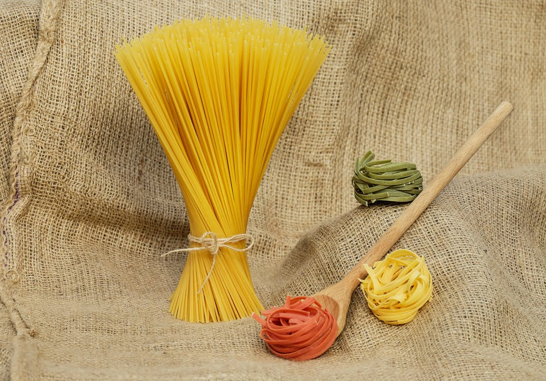 Pasta Beside Brown Wooden Laddle on Brown Knitted Textile