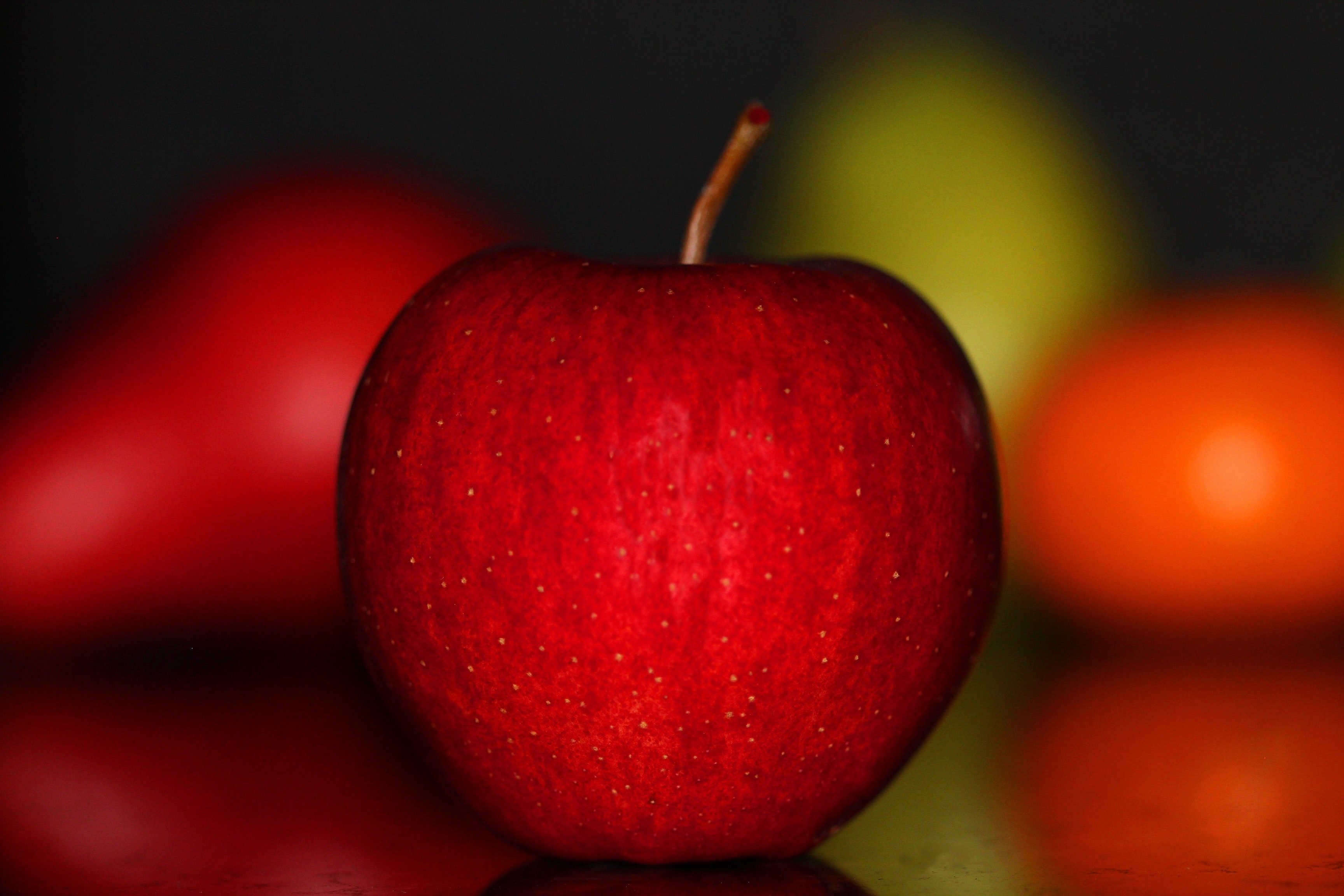 Shallow Focus Photography Of Red Apple On Gray Pavement
