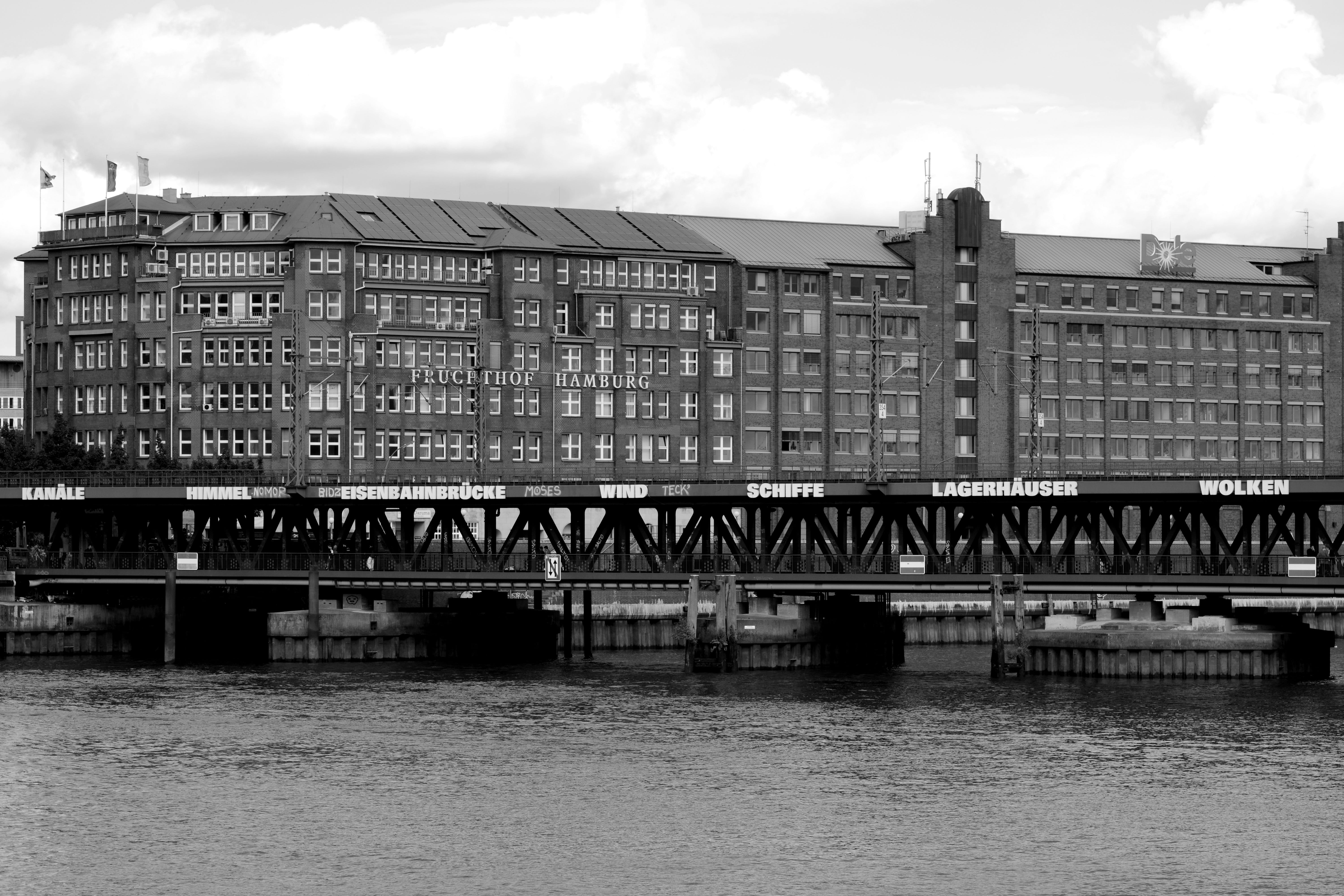 Grayscale Photo of Mid Rise Building Near Body of Water at Daytime