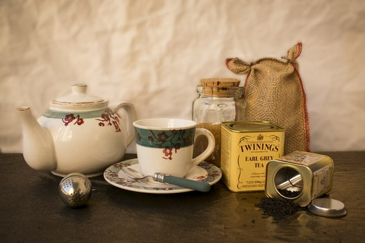 White and Green Ceramic Mug Beside Ceramic Teapot on Table