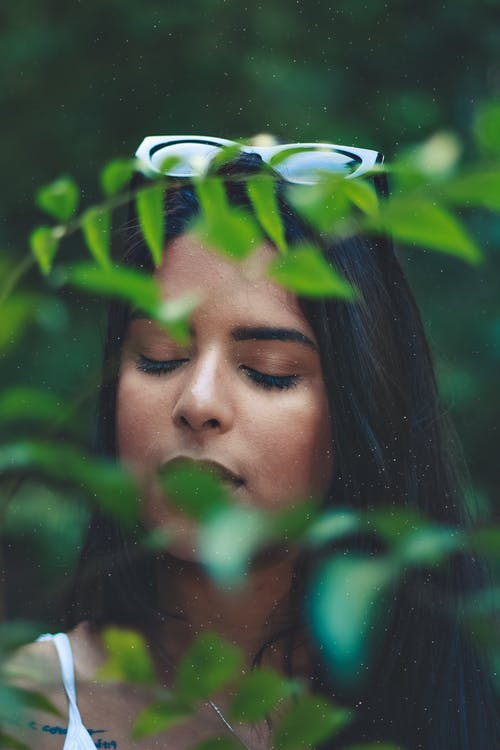 Photo of Woman Standing Behind Green-leafed Plant With Her Eyes Closed