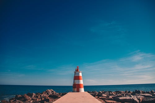 Orange and White Lighthouse on Dock