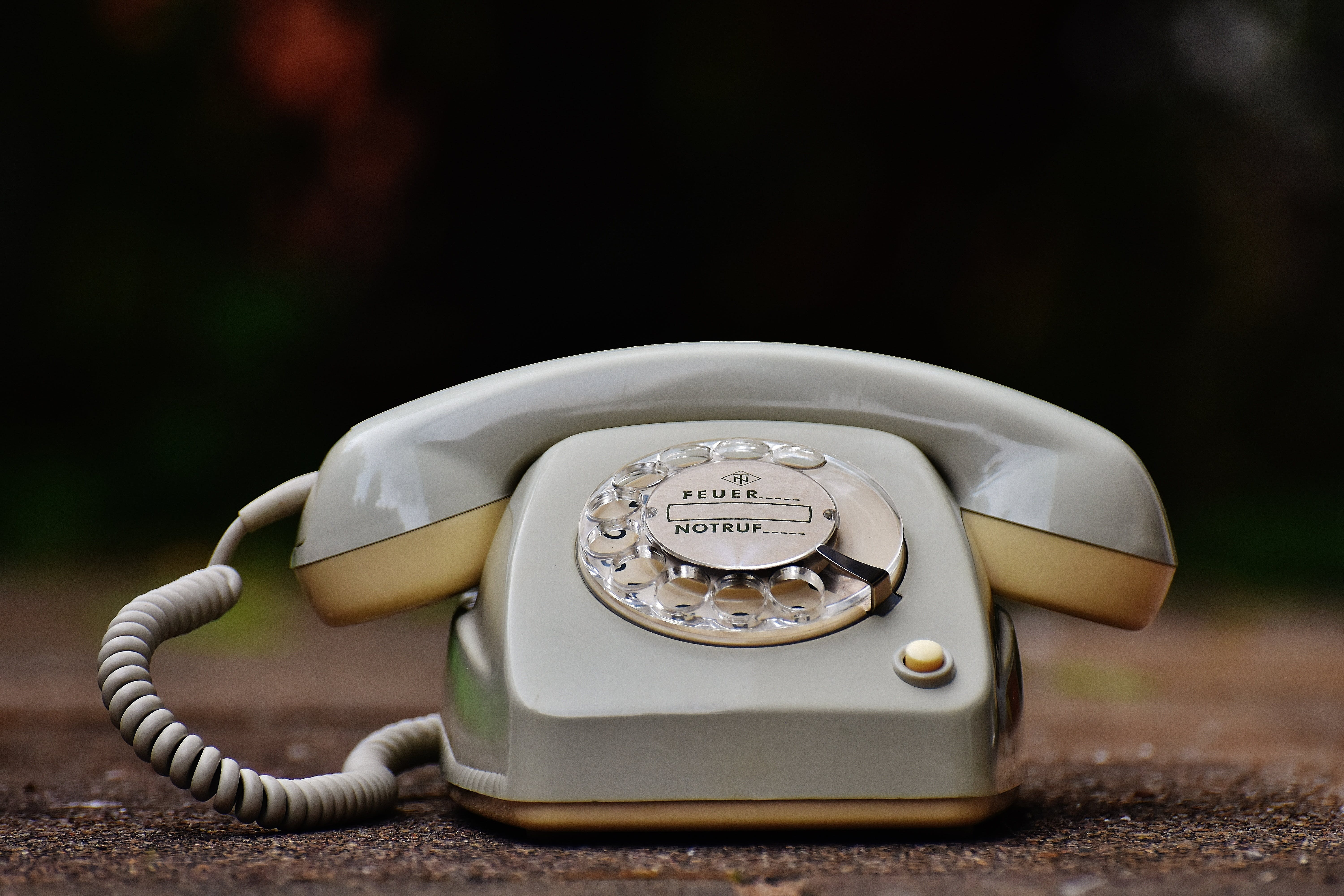 Gray Rotary Telephone on Brown Surface