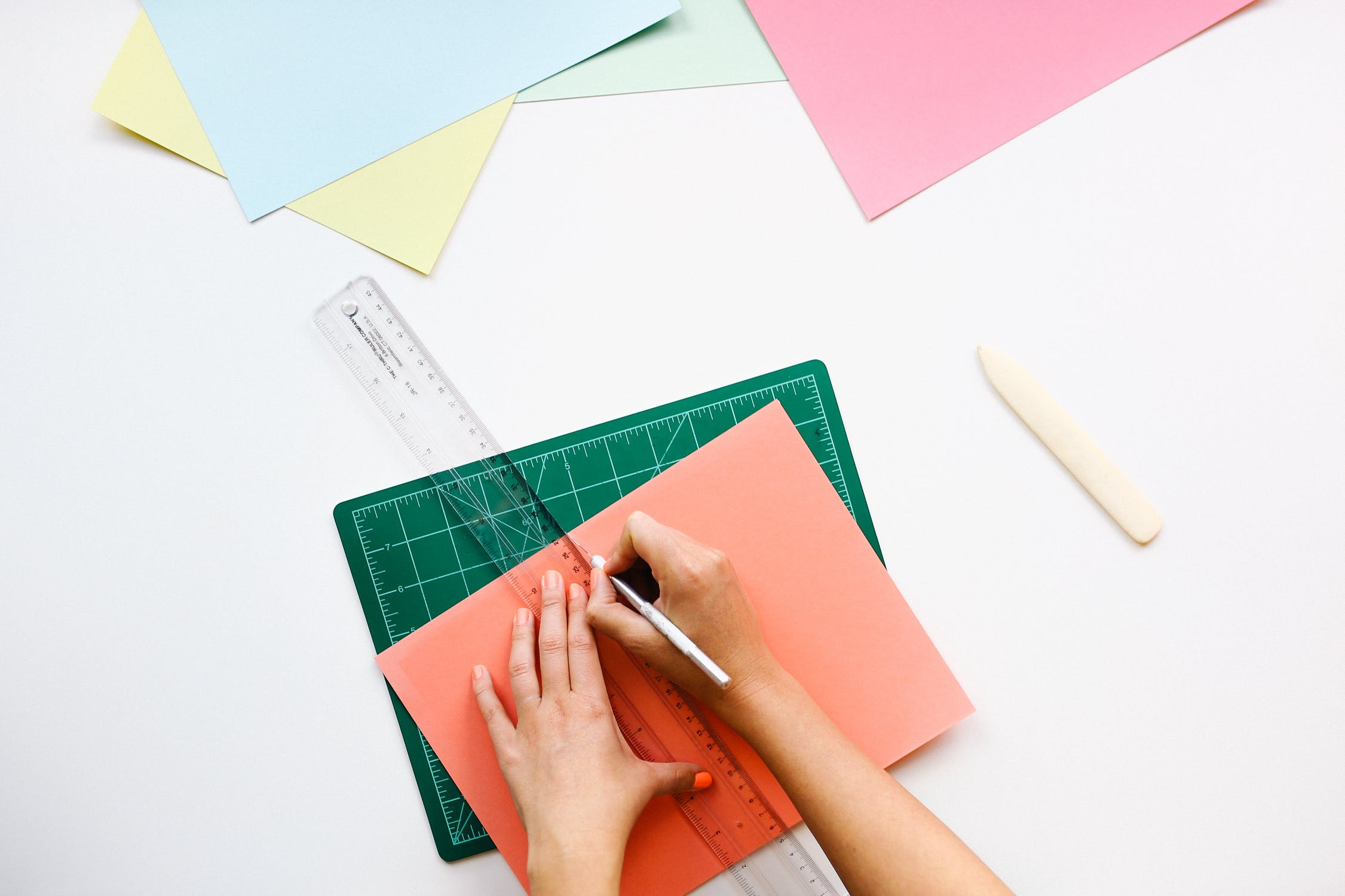 A person using a hobby knife and a ruler to cut colorful pieces of construction paper. Photo by pexels user Pixbay. Used courtesy of pexels.com
