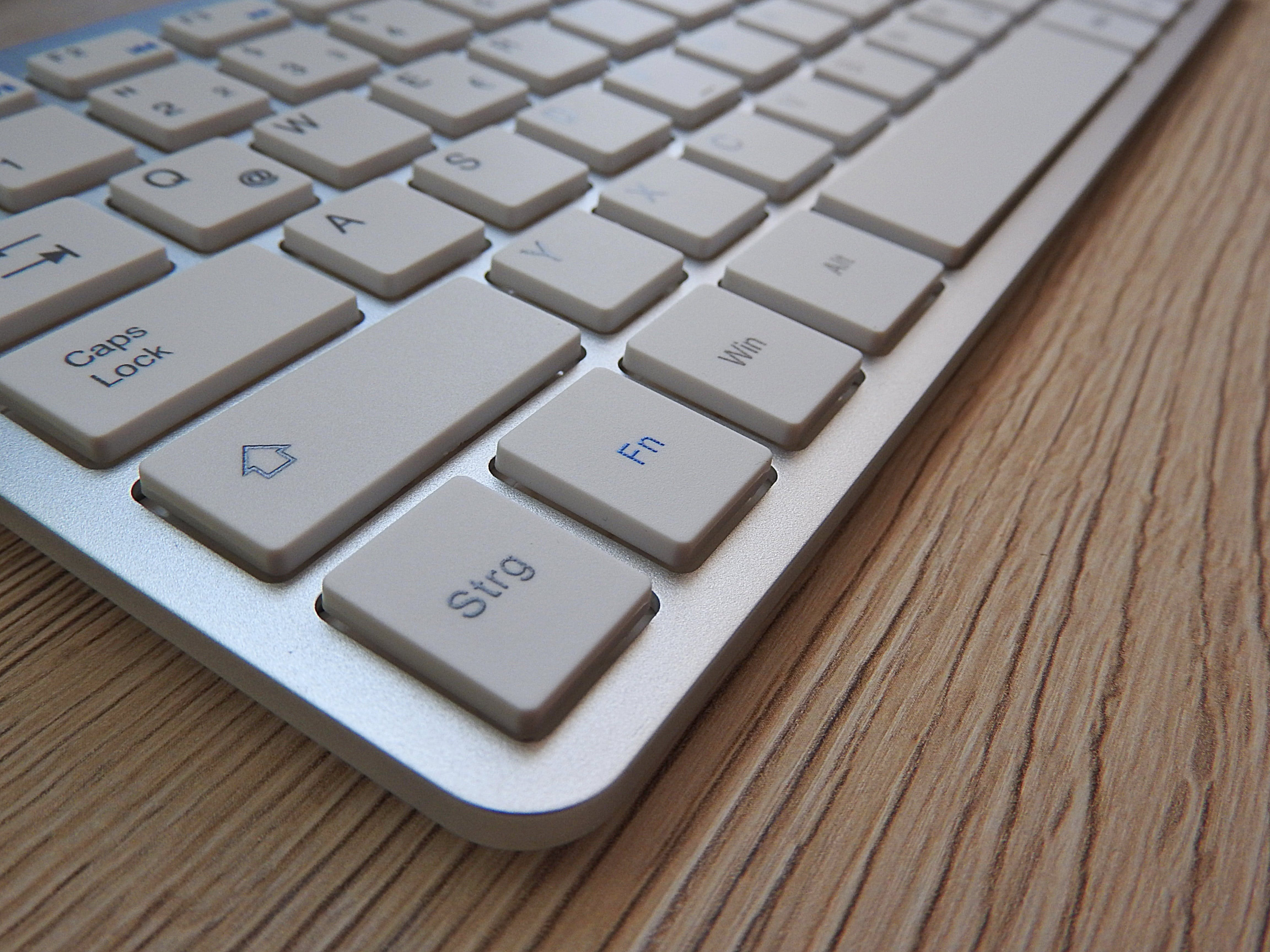 White Computer Keyboard on Brown Wooden Table