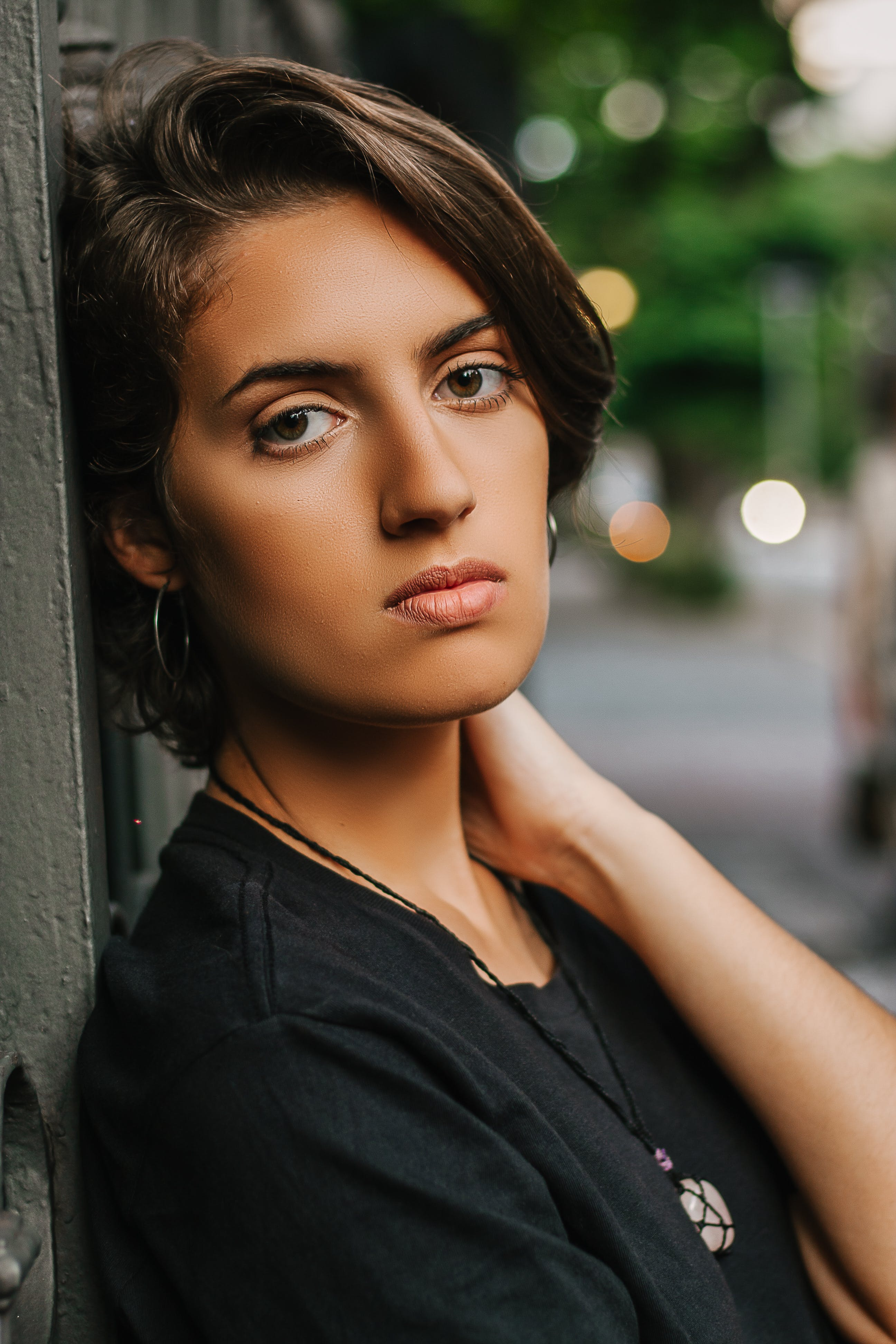 Woman Wearing Black Top Leaning On Wall