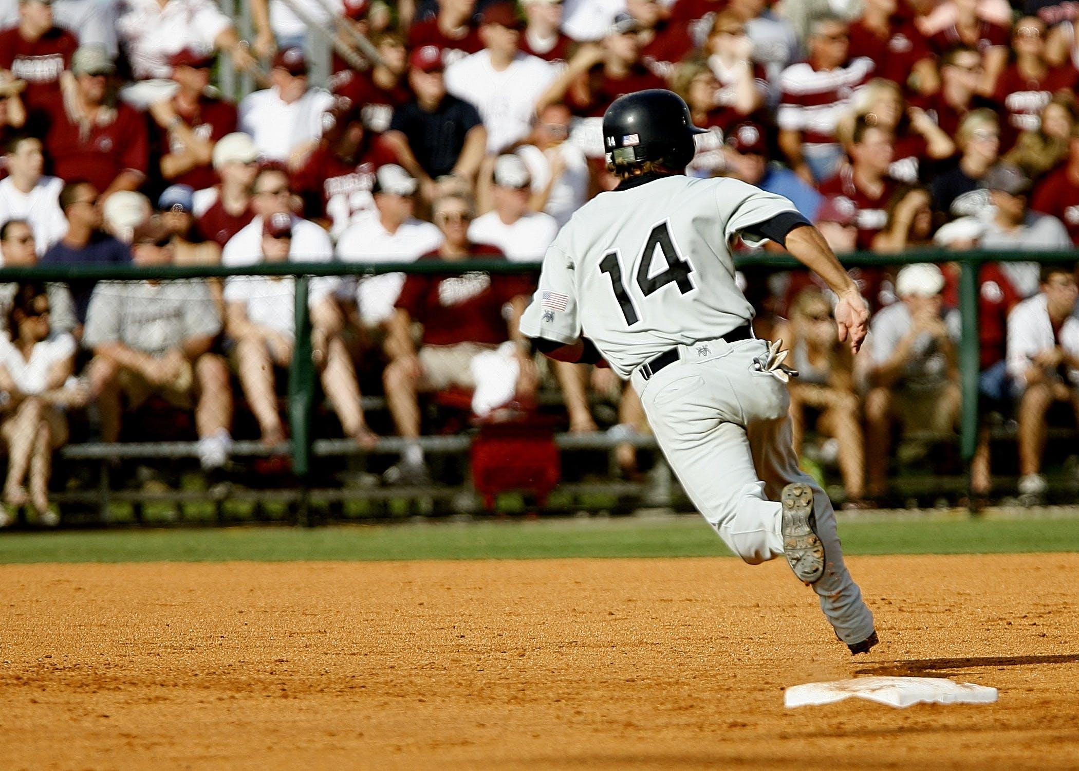 Baseball Player Number 14 Chasing Goal on Baseball Field