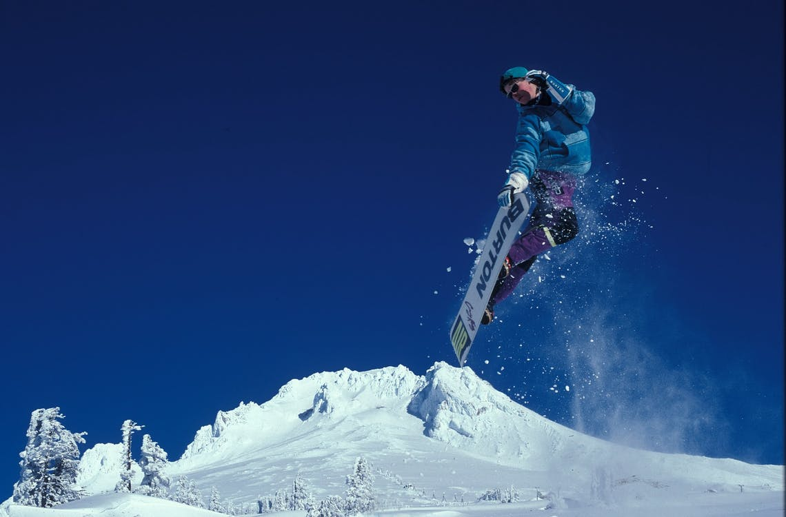a man with snowboard in the air after jumping from a snow ramp