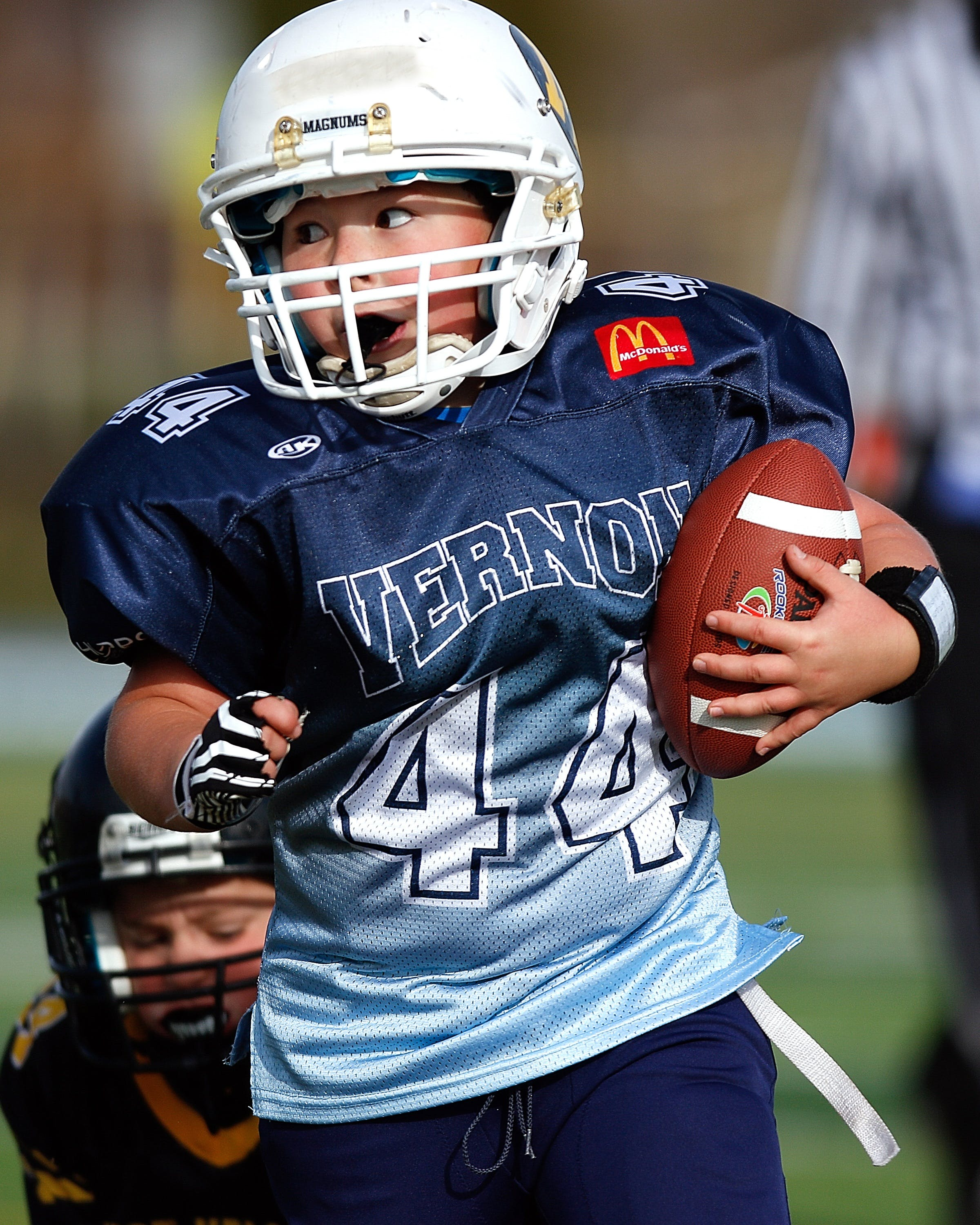 Boy Wearing Football Gear While Holding Football