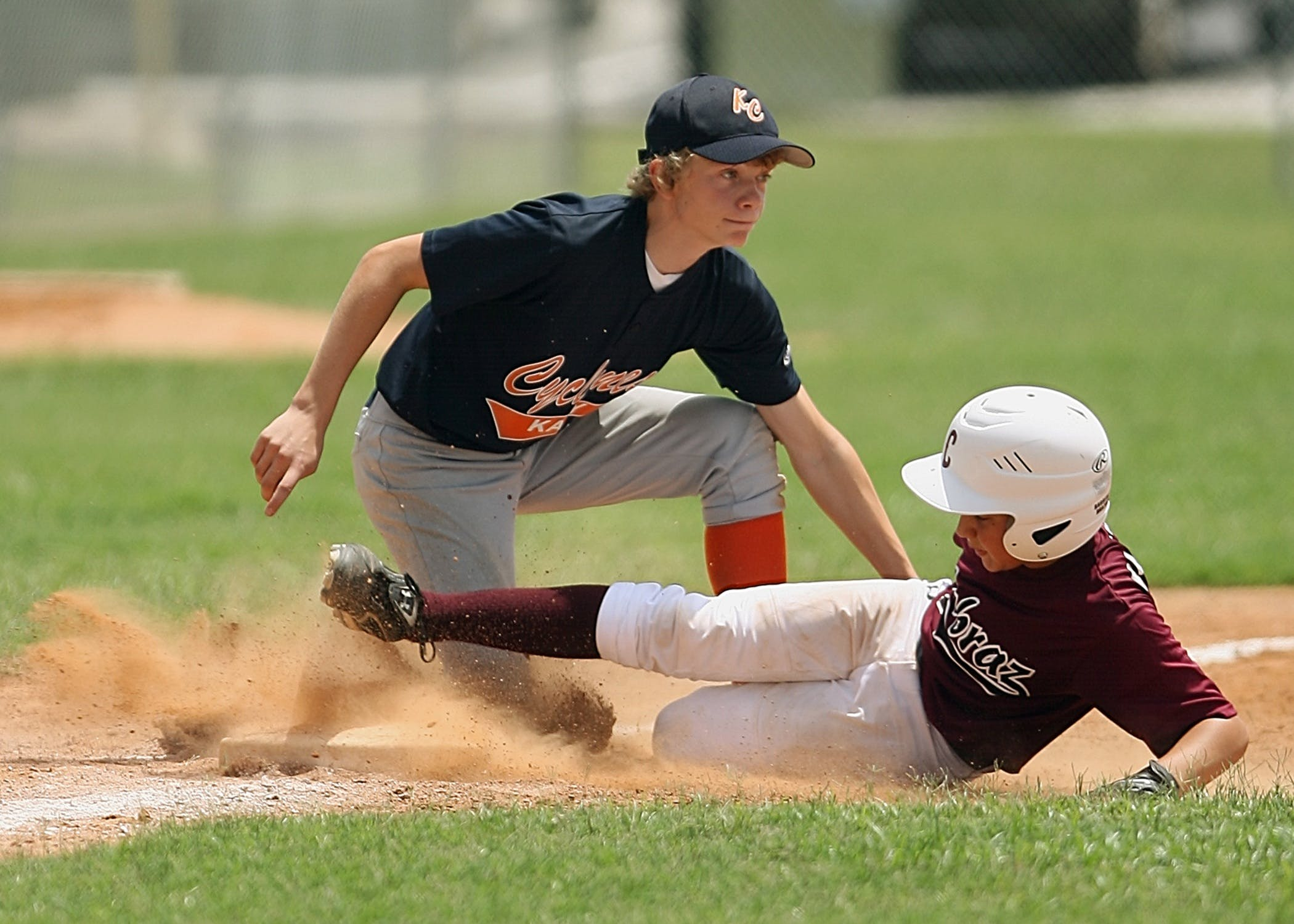 Man Kneeling Trays to Stop Man While Hes Sliding Towards Base