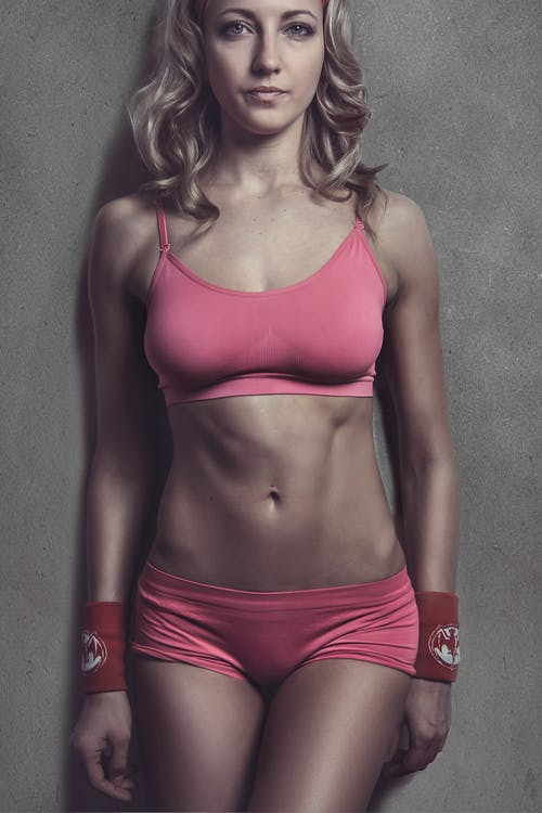 Woman Wearing Pink Fitness Wear Leaning on Wall