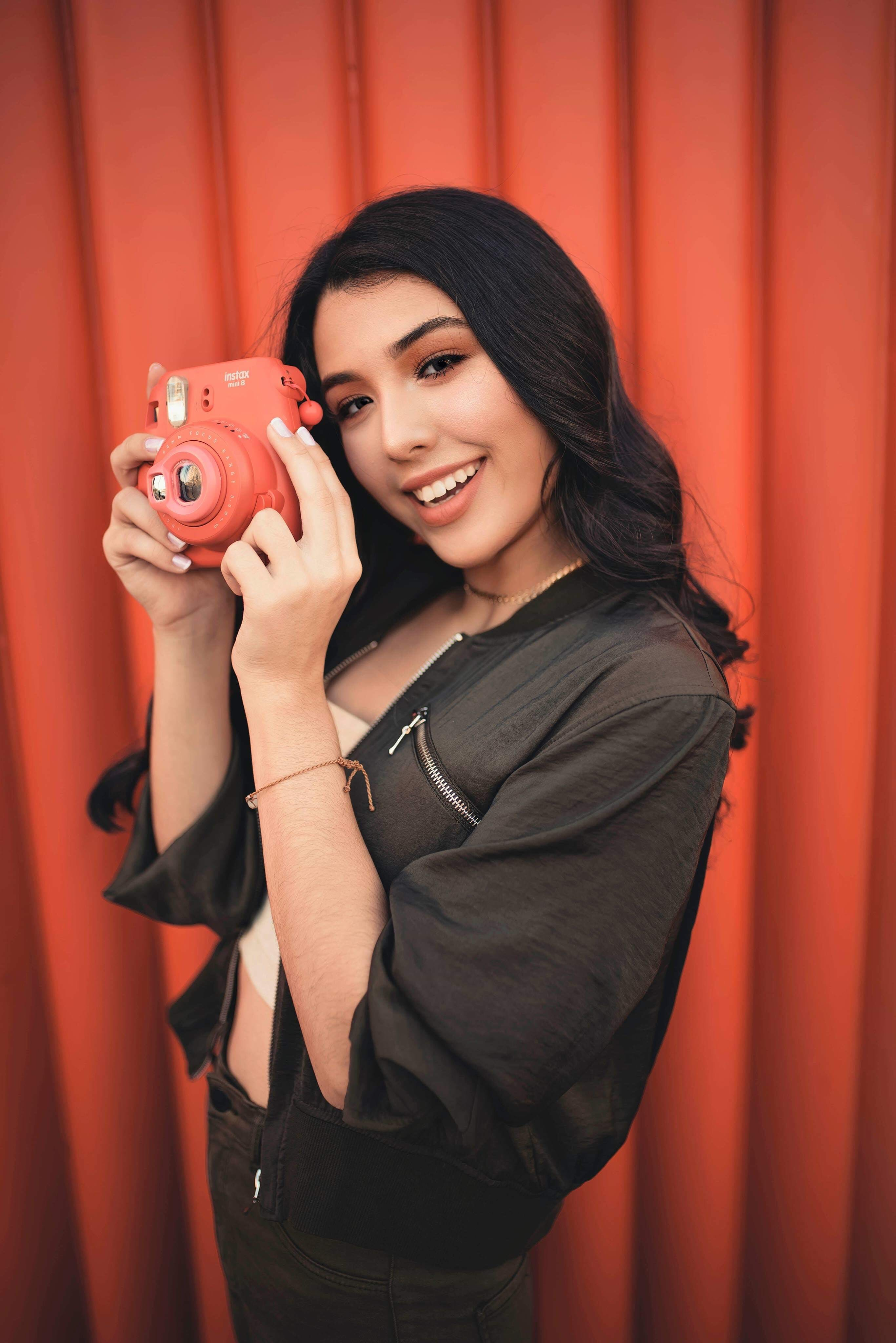 Woman Standing While Holding Red Instax Mini Camera