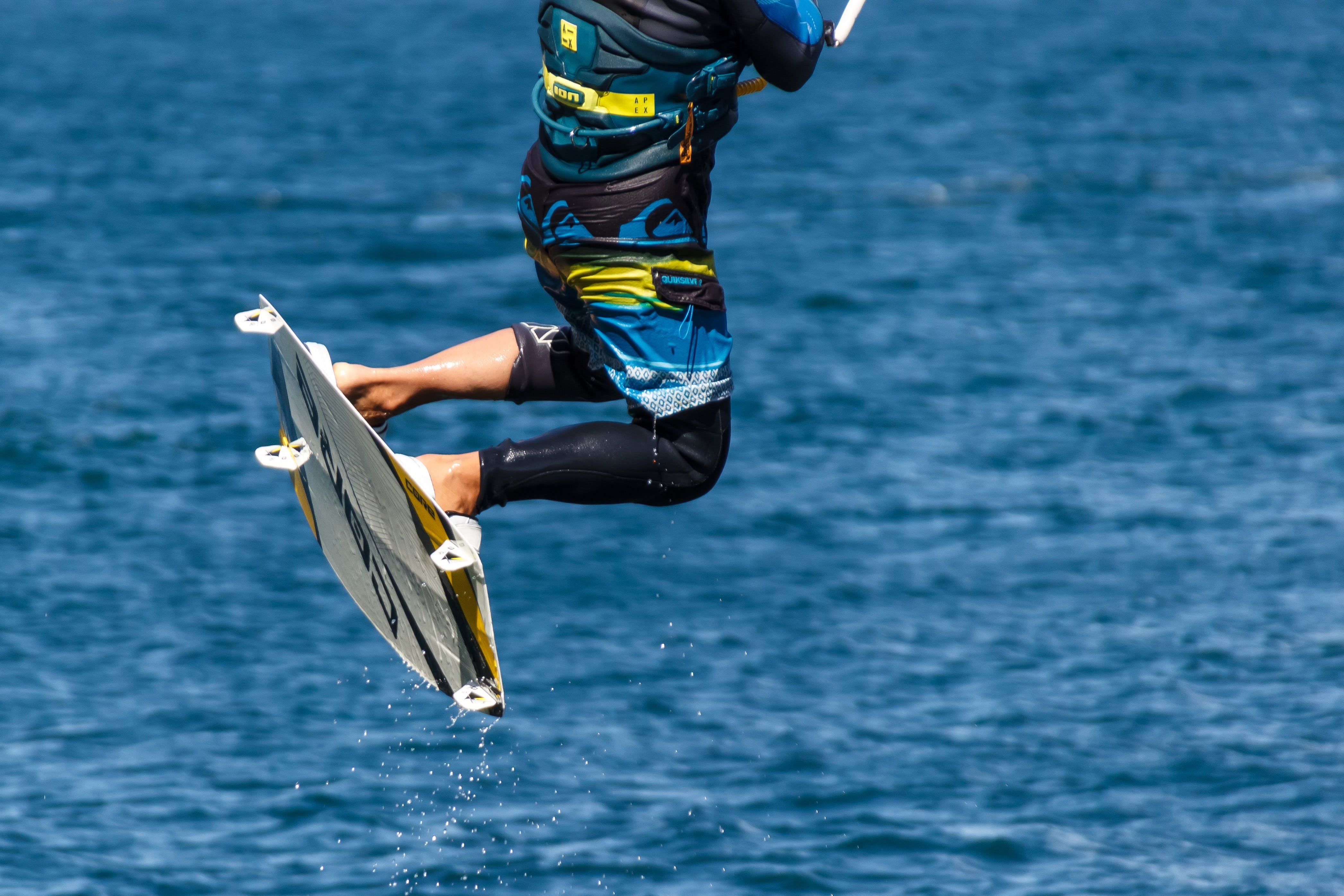Person in Blue and Black Board Shorts on White Wake Board