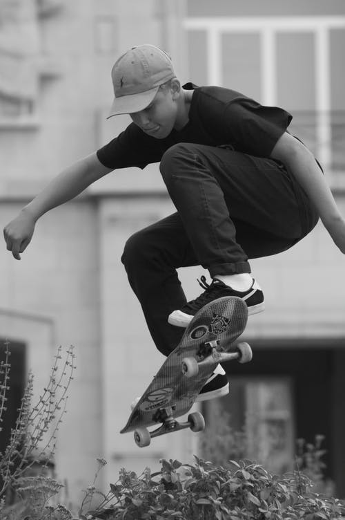 Man in Black Shirt Jumping With Skateboard