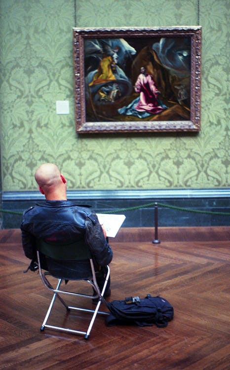 Man Sitting While Reading Book