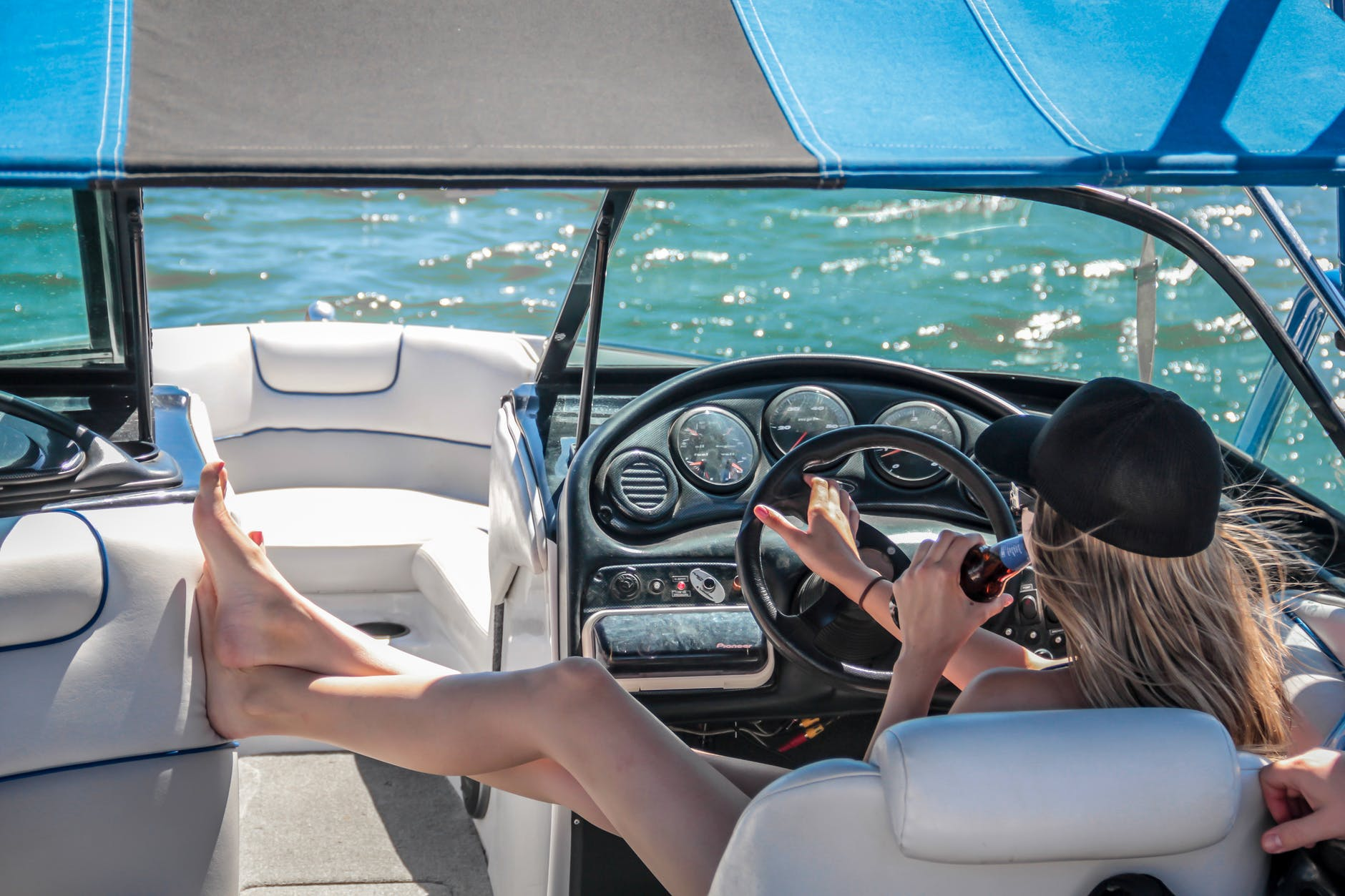 a woman steering the wheel of a saltwater fishing boat while drinking