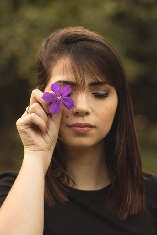 Shallow Focus Photo Of Woman In Black Crew Neck Shirt Holding Purple Flower
