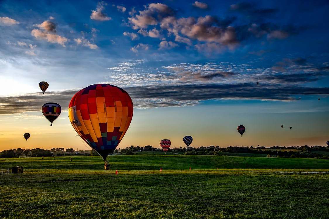Assorted-color Hot Air Balloons on Grass Field during Golden Hour