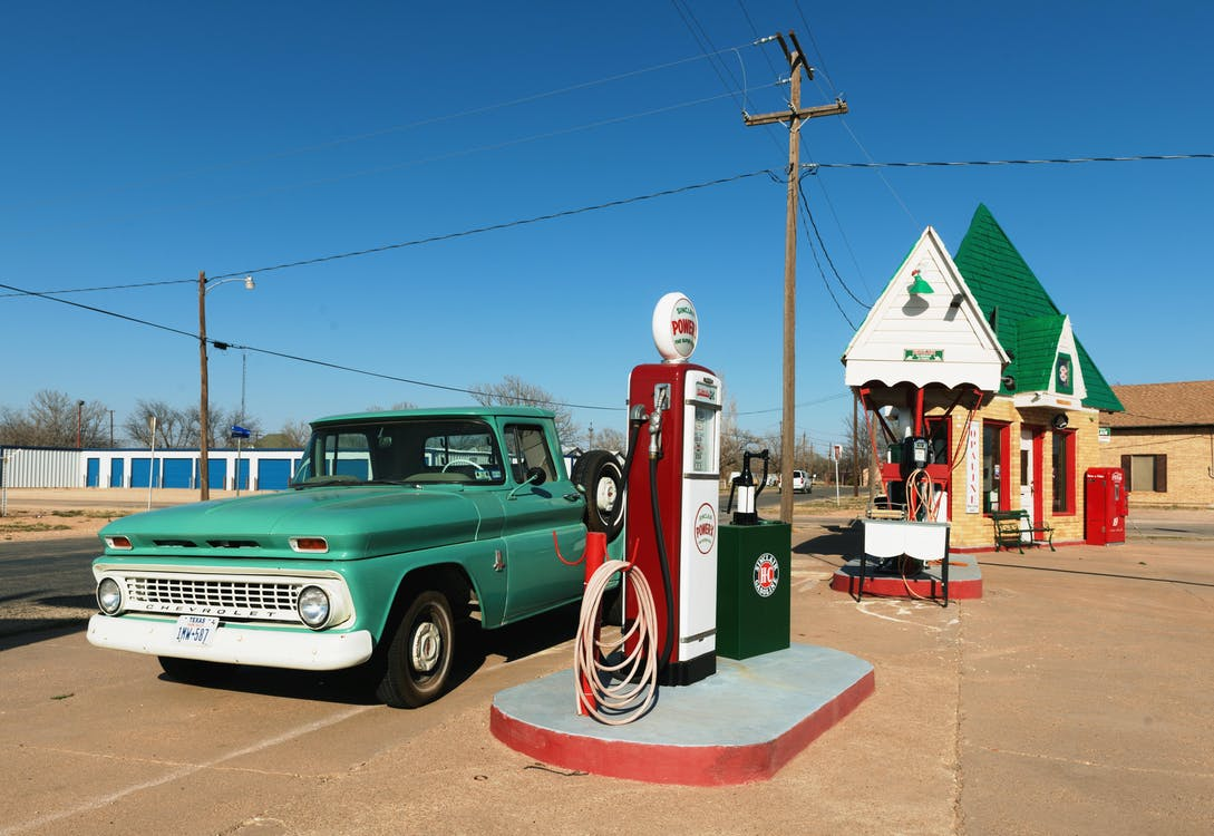 Green Single-cab Pickup Truck Beside a Gas Pump Station